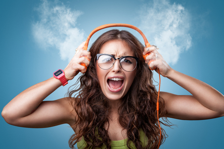 Photo pour Angry nervous girl in headphones listening to music and screaming loud blowing white smoke coming out of ears. Closeup portrait girl on blue background. Negative emotion facial expression feeling - image libre de droit