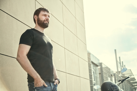 Portrait of biker men with beard in black shirt standing near a modern wall and looking away on sunset