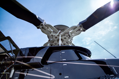 Close up of a screw of black with gray stripes bell 407 helicopter standing on green grass field in blue sky background.