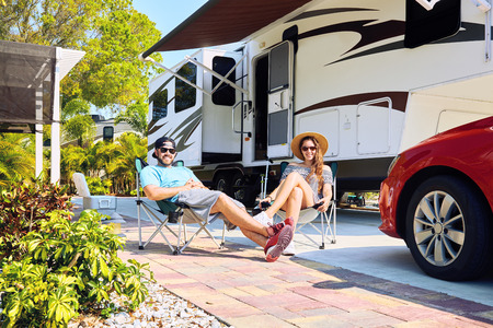 Photo pour Young couple sits near camping trailer,smiling.Woman and men in casual clothes relaxing on chairs near car and palms.Family spending time together on vacation near sea or ocean in modern rv park - image libre de droit