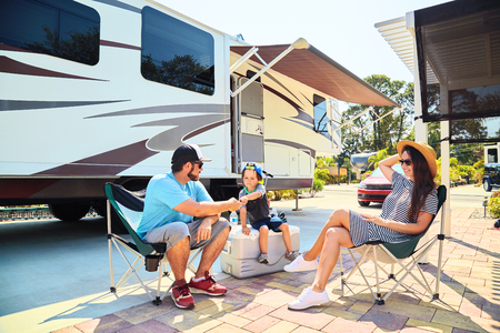 Photo pour Mother, father and son sitting near camping trailer,smiling.Woman, men, kid relaxing on chairs near car and palms.Family spending time together on vacation near sea or ocean in modern rv park - image libre de droit