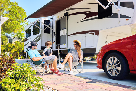 Photo pour Mother, father and son sitting near camping trailer, smiling.Woman, men, kid relaxing on chairs near car and palms.Family spending time together on vacation near sea or ocean in modern rv park - image libre de droit