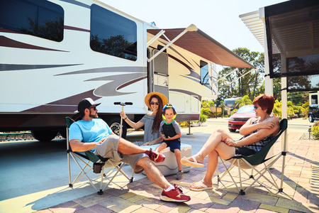 Foto de Mother,father,son and grandmother sitting near camping trailer,smiling.Woman,men,kid relaxing on chairs near car.Family spending time together on vacation near sea or ocean in modern rv park - Imagen libre de derechos