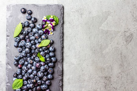 Berry fresh blueberries with mint leaves on black slate board