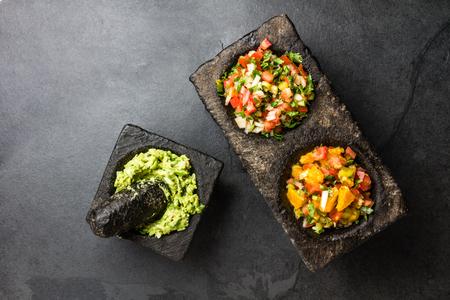Famous mexican sauces salsas - pico de gallo, avocado guacamole, salsa bandera mexicana in stone mortars on gray slate background.