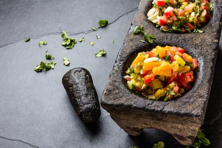 Famous mexican sauces salsas - pico de gallo, salsa bandera mexicana in stone mortars on gray slate background.