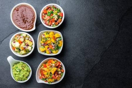 Traditional famous mexican sauces chocolate chili mole poblano, pico de gallo, avocado guacamole, salsa bandera, pinapple salsa, mango salsa on slate gray background.