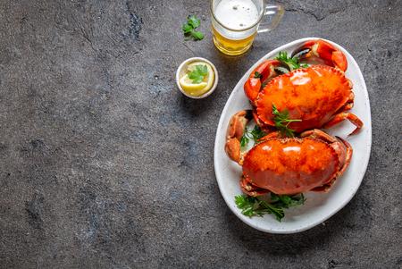 Foto de Whole cooked  crabs on white plate with lemon and beer. Gray concrete background. Top view - Imagen libre de derechos