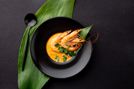 Seafood cream soup with shrimps decorated with tropical leaves. In black plate, on black background. Top view, copy space