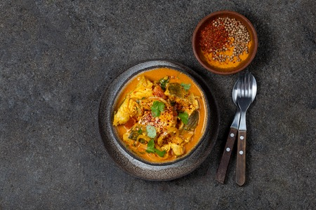 Photo pour INDIAN FOOD. Traditional KERALA FISH CURRY with naan bread, gray plate, black background - image libre de droit