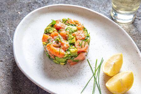 Foto de PERUVIAN FOOD. Salmon ceviche with avocado, spring onion and lemon on white plate served with white wine. - Imagen libre de derechos