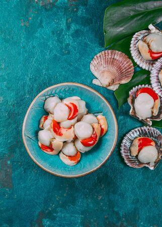 Foto de Raw fresh seafood shellfish scallops on blue background. - Imagen libre de derechos