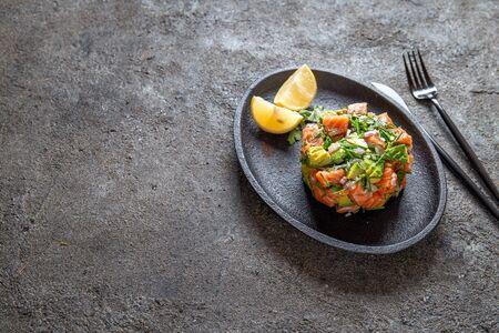 Foto de PERUVIAN NIKKEI FOOD. Salmon avocado ceviche on black plate, black background top view. - Imagen libre de derechos