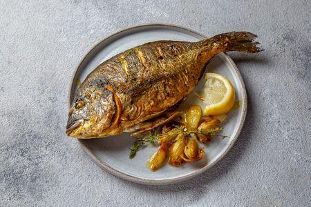 Photo pour Grilled sea bream or dorada on gray plate. Gray background. - image libre de droit