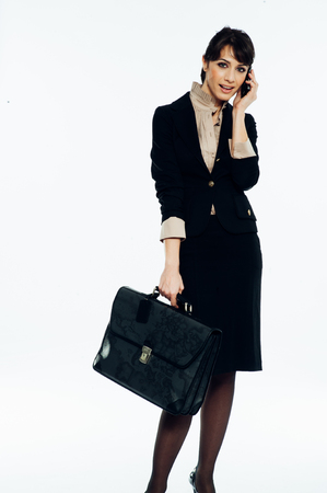 Young caucasian brunette suit dressed business woman talking with a vintage smartphone. Standing up. Studio shot.