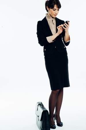 Young caucasian brunette suit dressed business woman chatting with a vintage smartphone. Standing up. Studio shot.