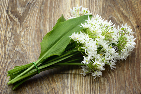 Bunch of ramson wild garlic flower heads and leaves on wooden table.
