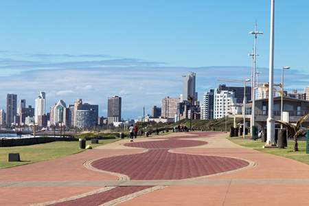 Photo for Quiet early morning paved promenade against city skyline and blue cloudy sky in Durban, South Africa - Royalty Free Image