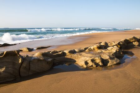 Photo pour Smooth beach sand after water recedes with smooth rocks showing erosion - image libre de droit