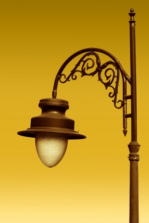 Aged gilded street lamp over yellow background