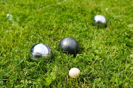 Bocce balls sitting in the green grass, close to the target. -shallow depth of field.-