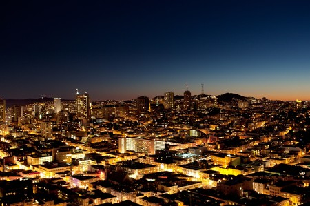 A view of a city at night with a sunset on the horizon - San Jose