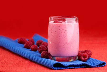 A raspberry smoothie on a red and blue background