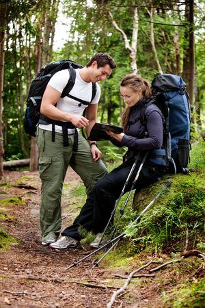 A couple on a backpacking camping trip looking at a map
