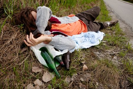A drunk man laying in the ditch with beer bottles