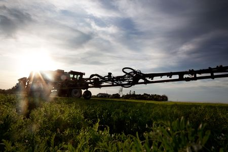 A silhouette of a high clearance sprayer on a field with solar flare.