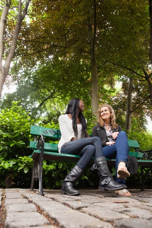 Low angle view of two young relaxed female friends chatting in the park