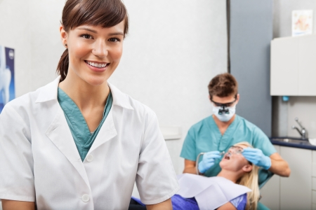 Portrait of dental assistant smiling with dentistry work in the background