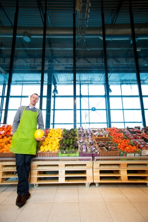 An owner of a grocery store standing by fruits and vegetables