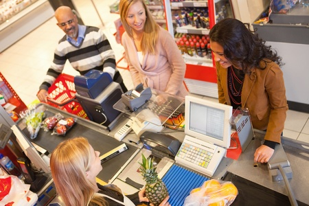 Photo pour High angle view of cashier with a line of people at the check-out counter - image libre de droit