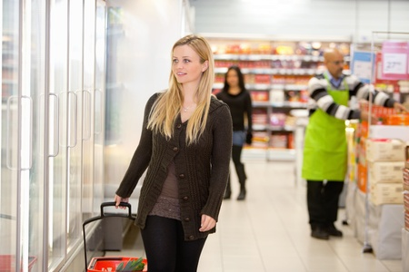 Smiling woman walking in shopping centre, looking in refrigerator with people in the background