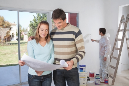 Photo pour Couple going through house plan while painter in the background - image libre de droit