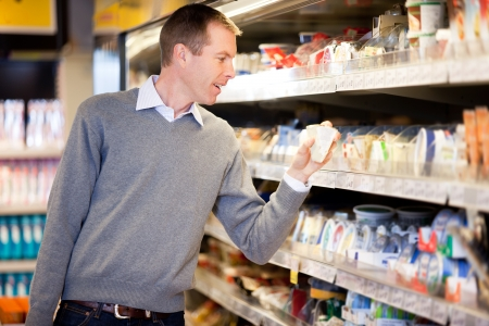 A man buying cheese and comparing prices in a grocery store