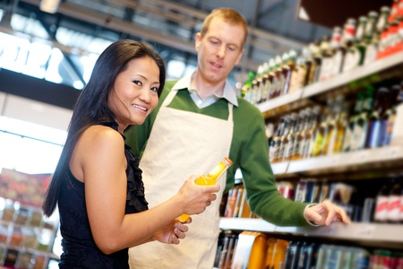 An asian woman in a grocery store receiving help from a store clerk