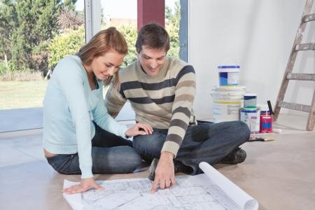 Photo pour Mature man showing blueprint of their new house to his wife - image libre de droit
