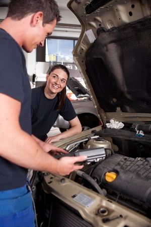 A man and a woman mechanic team doing service on a car in a garage
