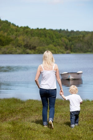 A mother walking with her son hear a lake with a small boat