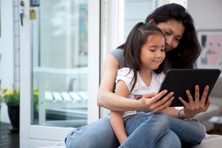 Mother and Daughter having fun on a digital tablet in a home interiorの写真素材