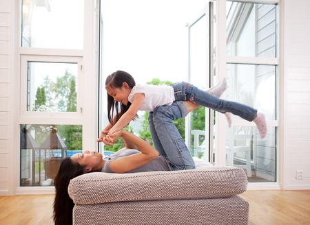 Playful mother giving daughter an airplane ride with arms and feet