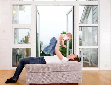 Mother holding son over head playing and having fun at home