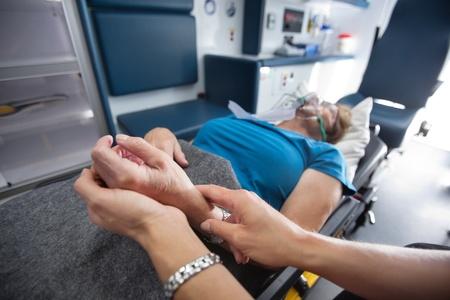 Detail of EMT worker measuring pulse on senior woman patient in ambulance