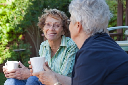 Two senior women enjoying a warm drink outdoors