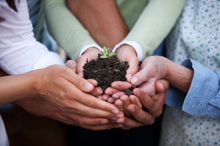 Group of people of all ages holding a plant in dirt