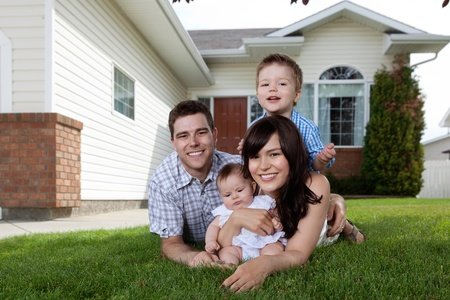 Foto de Portrait of happy family lying down on grass in front of house - Imagen libre de derechos
