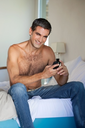 Photo pour Portrait of shirtless man using cell phone - image libre de droit