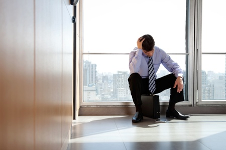 Young business man sitting in depression with hand on head